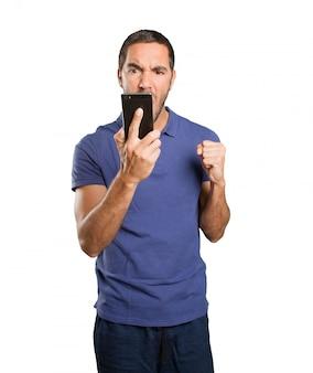 Gniewny młody człowiek trzyma telefon komórkowy na białym tle
