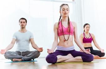Grupa osób uprawiających jogę w domu w pozycji lotosu.