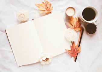 Jesienią koncepcji stylu życia, puste notebooka i kawy z jesieni pozostawia ozdoby na białym tle łóżko pościel