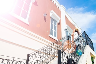 Klasyczny budynek z atrakcyjną perspektywą i turystyczną kobietą w białej sukni i kapeluszu