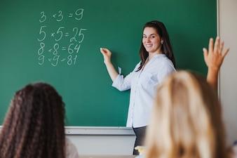 Kobieta nauczyciel stoi z tablicy