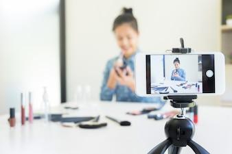 Kobieta obecny produkt piękna i emitować wideo na żywo do sieci społecznej przez internet w domu, koncepcja blogger piękna.