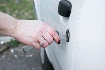Kobieta otwierania drzwi samochód drzwi z kluczem