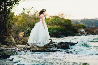 Kobieta w sukni ślubnej na brzegu rzeki