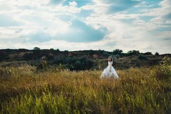 Kobieta z sukni ślubnych spaceru na łące