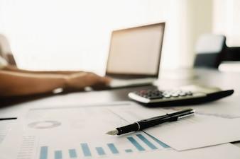 Koncepcją biznesową z miejsca na kopię. Biuro biurko tabeli z piórem fokus i analizy wykresu, komputer, notebook, filiżankę kawy na biurko.Vintage dźwięk Retro filtra, selektywne fokus.