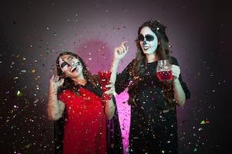 Koncepcja Halloween z kobietami, napojami i konfetti