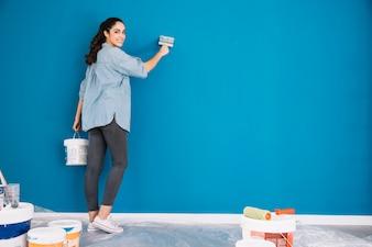 Koncepcja malowania z kobietą malowanie niebieską ścianą
