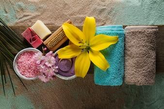 Koncepcja Spa. Widok z góry pięknych produktów spa z miejscem na tekst. Olejek eteryczny z pięknymi kwiatami, ręczniki, sól do kąpieli i ręcznie robione mydło.