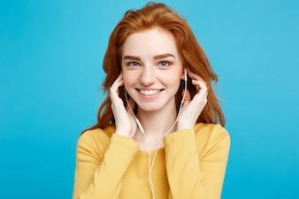 Koncepcja stylu życia - Portret wesołej szczęśliwy imbir czerwony włosy dziewczyna cieszyć słuchanie muzyki przez słuchawki radosne uśmiecha się do aparatu. Pojedynczo na Niebieskim Tle Pastelowe. Skopiuj miejsce.