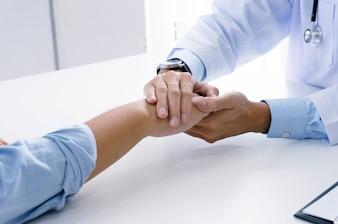 Lekarz posiadający dłoń pacjenta i uspokajający swojego męskiego pacjenta pomagając koncepcji ręki