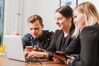 Ludzie siedzący przy biurku pracy na laptopie