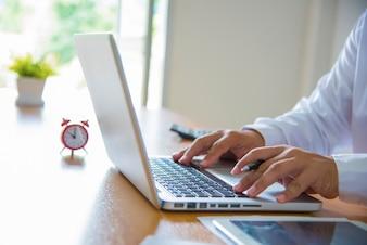 Mężczyzna biznesowych przy użyciu komputera przenośnego. Mężczyzna ręcznie wpisując na klawiaturze laptopa