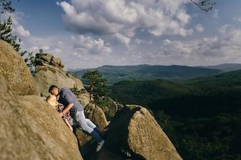 Mężczyzna całuje kobietę stojącą przed pięknym górskim krajobrazem