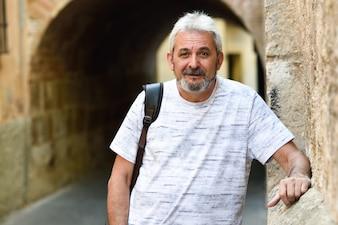 Mężczyzna dojrzałym uśmiecha się spojrzenie na aparat fotograficzny w tle miejskich