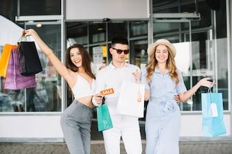 Mężczyzna i dwie kobiety z papierowymi torebkami