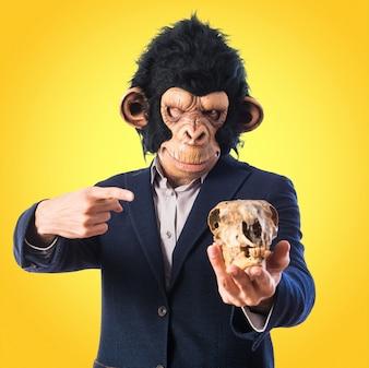 Mężczyzna Monkey gospodarstwa czaszki na kolorowe tło