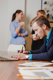 Mężczyzna w garniturze siedzi na rysunku biurko