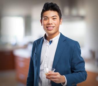 Mężczyzna w garniturze z drinkiem w ręku