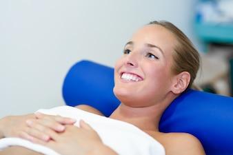 Młoda kobieta pacjenta na łóżku w centrum fizjoterapii.