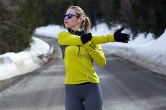 Młoda kobieta rozciąga się i przygotowuje się do biegania na drodze.
