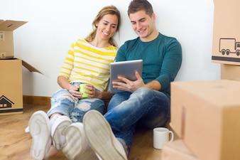 Młoda para z cyfrowego tabletu w nowym domu