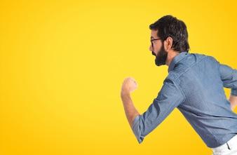 Młody człowiek hipster działa szybko na białym tle na kolorowe tło
