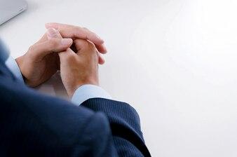 Młody mężczyzna czeka na wywiad i trzymając się za ręce złożone na stół.