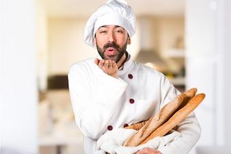 Młody piekarz gospodarstwa chleb i wysyłanie pocałunek w kuchni