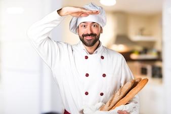 Młody piekarz trzyma chleb i coś pokazującego w kuchni