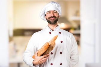 Młody piekarz trzyma chleb w kuchni