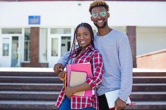Młodzi ludzie z książkami ubiegającymi się w pobliżu uniwersytetu