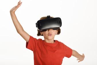 Mała dziewczynka patrząc w okulary VR i gestykulując rękami.