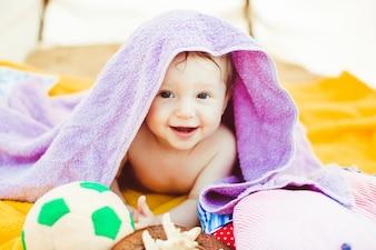 Mały chłopiec leży pod fioletowym ręcznikiem