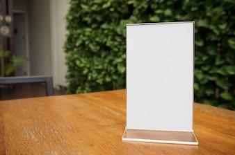 Makieta Ramka menu stoi na drewnianym stole w kawiarni barowej. miejsca na tekst. montaż na wyświetlaczu produktu