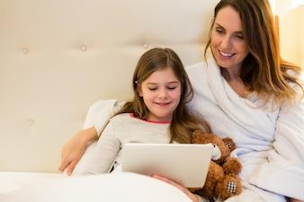 Matka i córka przy użyciu cyfrowego tabletu w sypialni