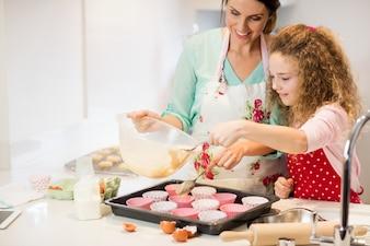 Matka i córka w kuchni przygotowując ciastko
