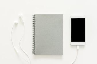 Minimalna przestrzeń robocza - Kreatywne płaskie lay zdjęcie pulpitu roboczego biurko z szkicownik i telefon komórkowy z pustym ekranem na przestrzeni kopii na białym tle. Widok z góry, fotografia płaska.