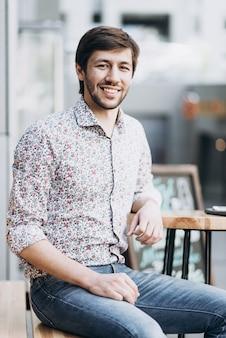 Modny uśmiechnięty mężczyzna w miejskim otoczeniu