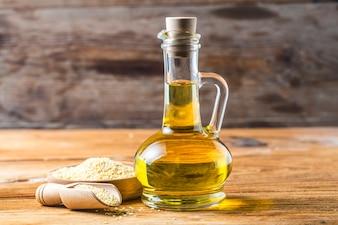 Nasiona sezamu i butelki z olejem na starym drewnianym stole, olej z sezamu w szklanym dzbanku.