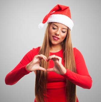 Nastolatka z Santa Claus kapelusz pokazano gest miłości