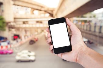 Osoba korzystaj? Ca ze smartfonu na bia? Ym ekranie posiadacza strony z rozmyte d? Ugo? Ci ruchu na ulicy miasta w Bangkoku Tajlandii.