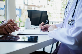 Pacjent słucha uważnie lekarzowi płci męskiej, wyjaśniając objawy pacjenta lub zadając pytanie, podczas gdy w konsultacji dyskutują o pracy papierkowej