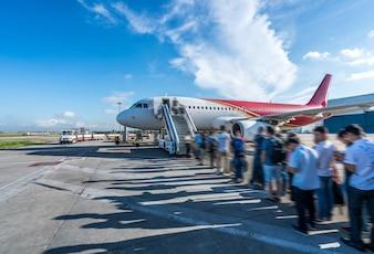 Pasażerowie czekają w kolejce na pokład samolotu