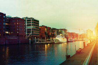 Piękny obraz słońca w mieście portowym z wodą, statków i mostu. Tonowanie. Hamburg, Niemcy.