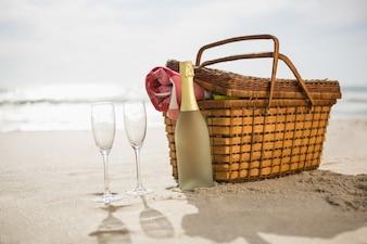 Piknik kosz, butelka szampana i dwa kieliszki na piasku