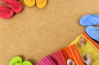 Plaża tło z ręcznik i klapki