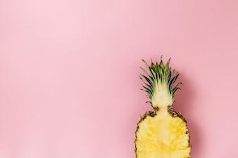 Pół plasterka pięknego świeżego apetycznego smacznego ananasa na różowym tle. Widok z góry. Poziomy. Skopiuj miejsce. Konceptualistyczny.