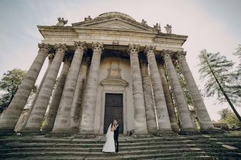 Po prostu żonaty para całuje ze starym budynku tle
