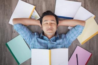 Portret azjatyckich człowieka drzemki na podłodze wśród książek